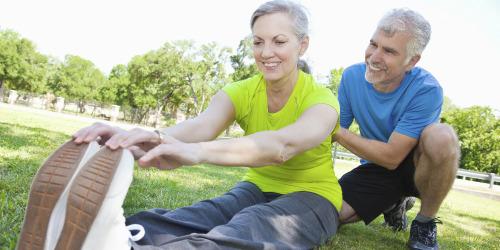 Женщина с наушниками на пробежке смотрит время на наручных часах