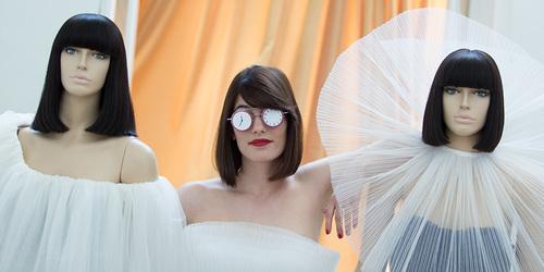 Frau mit einer Brille, die aus Uhren anstatt Gläsern besteht, steht zwischen zwei Schaufensterpuppen.