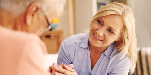 Eldre kvinne sitter sammen med yngre kvinne – hvordan pleie din kjære som har psykiske helseutfordringer