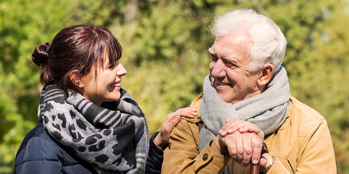 Older man sitting outside with younger woman – financial help for caregivers