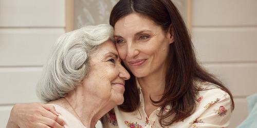 Yngre kvinne klemmer eldre kvinne – finn ut hvorfor TENA-produktene er de beste for din kjære