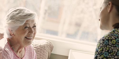 Yngre og eldre kvinne snakker sammen – lær om hva som forårsaker inkontinens