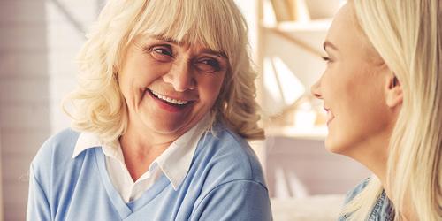 Eldre kvinne ler sammen med yngre kvinne – hvordan du kan hjelpe din kjære som har inkontinens
