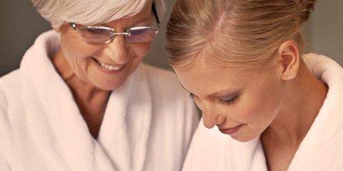 Eldre kvinne pleier huden sammen med yngre kvinne – gi din kjære den beste hygienen