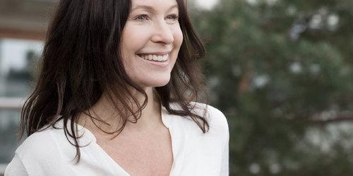 Pruunide juustega naine kaamerasse naeratamas