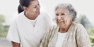 Verpleegkundige en oudere vrouw genieten van elkaars gezelschap