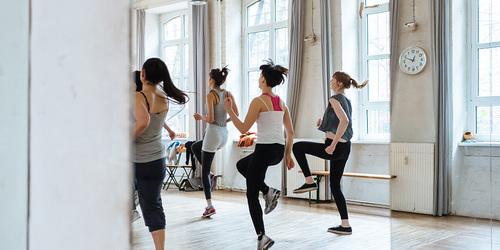 Vier Frauen beim Aerobic-Workout, von hinten aufgenommen.