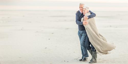 Een oudere man slaat zijn armen om zijn vrouw om haar warm te houden terwijl ze over een winderig strand lopen