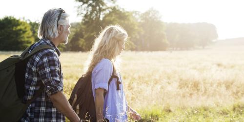 Чоловік та жінка зрілого віку з рюкзаками крокують сонячним полем