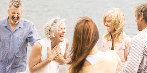 Four mature friends are laughing on the beach