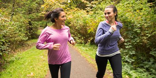 Twee vrouwen die in het bos hardlopen