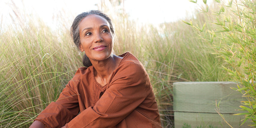An serene senior woman sits in a sunny field surrounded by high grass
