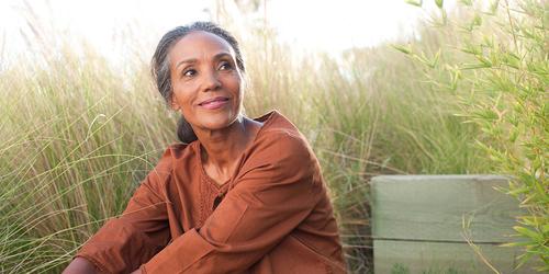 Een serene oudere vrouw zit in een zonnig veld, omringd door hoog gras