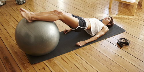 Henkilö tekemässä pilatesharjoitusta makuulla, jalat pilatespallon päällä.
