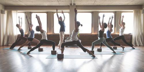 Acht Personen beim Yoga.