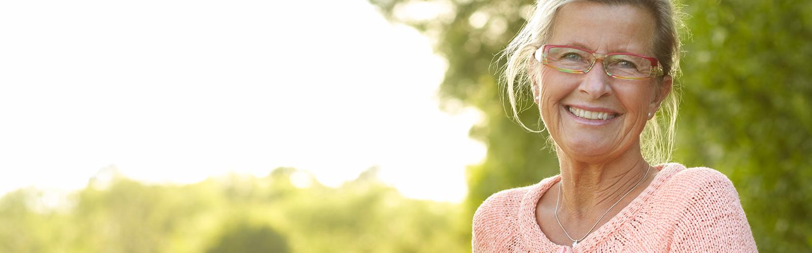 Счастливая женщина старшего возраста с велосипедом надевает шлем