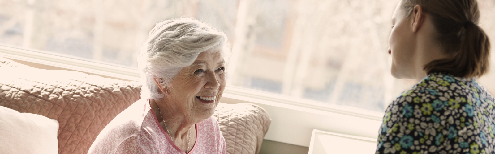 Younger woman and older woman talking - earn about what causes incontinence