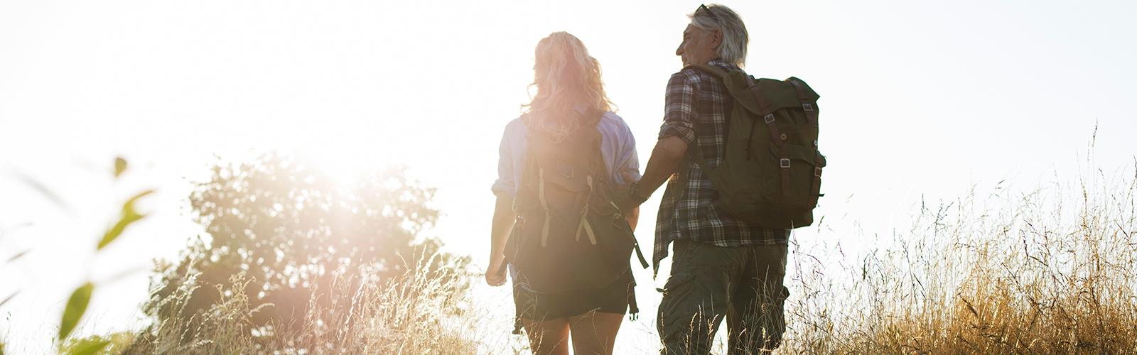 Muškarac i žena zrelih godina šeću kroz sunčano polje