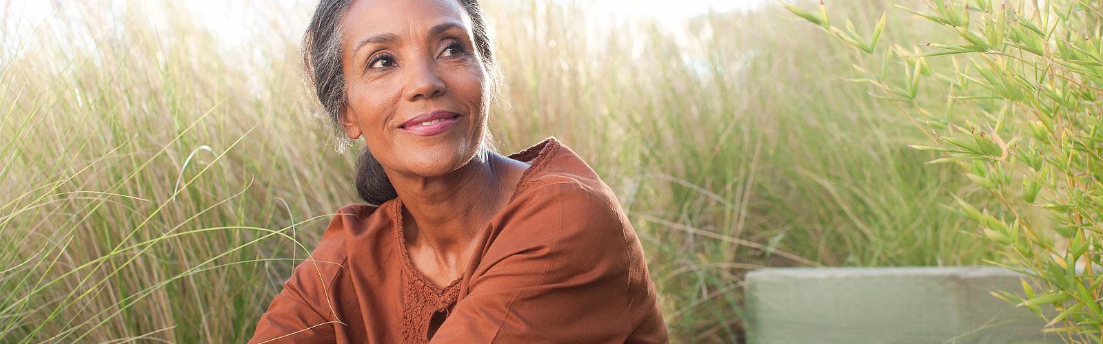 Egy derűs idős hölgy ül a napos réten, a magasra nőtt fűben