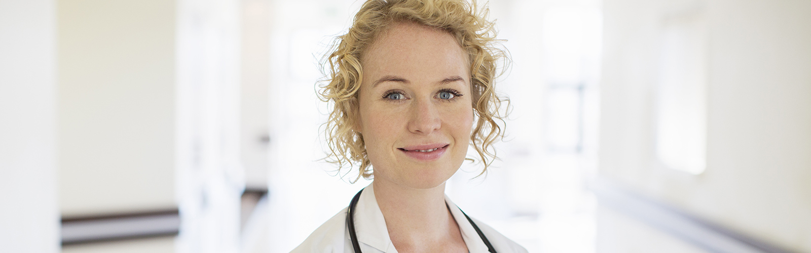 A blonde female doctor with a stetoscope smiles in a hospital corridor
