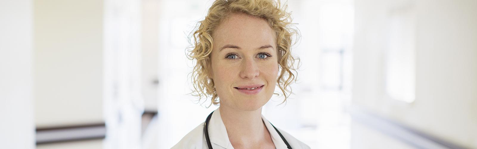 Svetlolasa zdravnica s stetoskopom se smeji na bolnišničnem hodniku