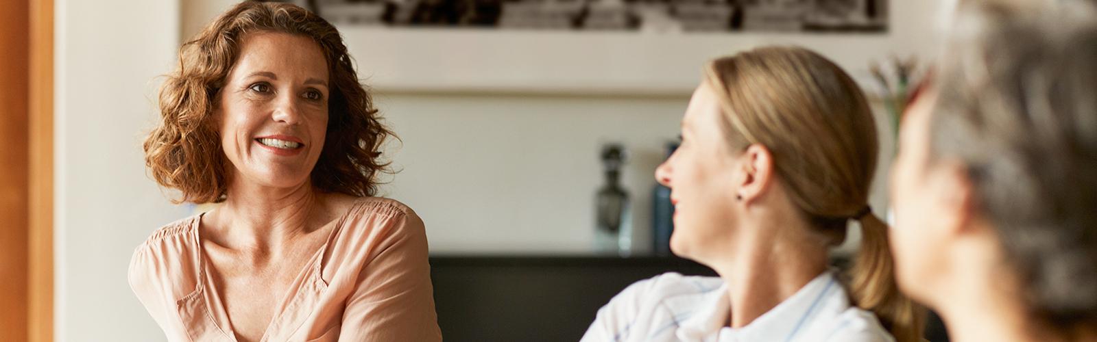 Три жінки зрілого віку сидять на дивані у вітальні, насолоджуючись розмовою