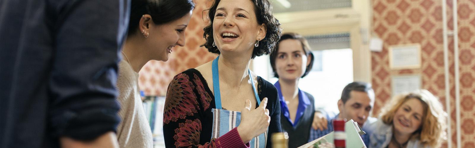 Egy főzőoktató hölgy kíváncsi tanulók gyűrűjében a konyhában