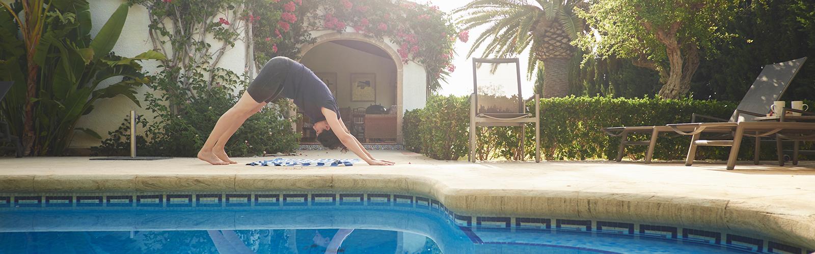 Frau, die Yoga neben einem Swimmingpool praktiziert
