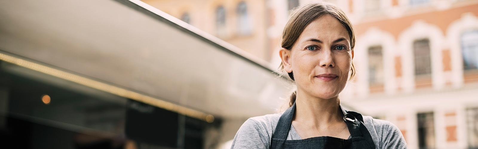 Bilde forfra av selvsikker kvinnelig kokk som står ved matvogn i by