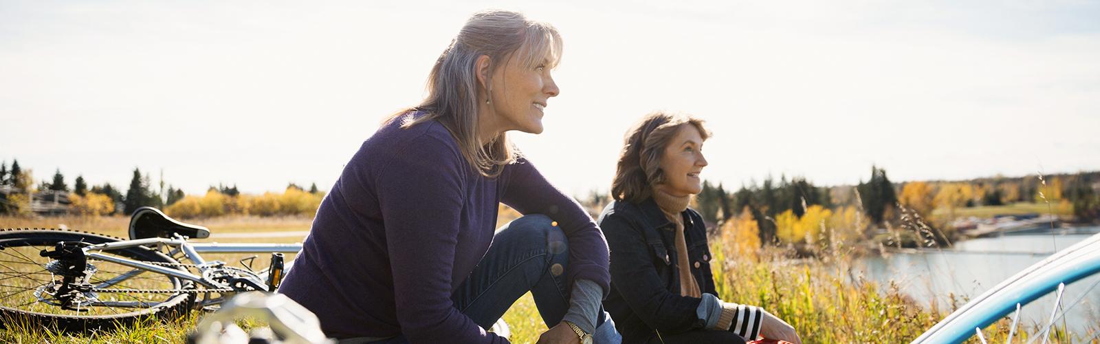 Dvi moterys su dviračiais sėdi saulėtoje pievoje