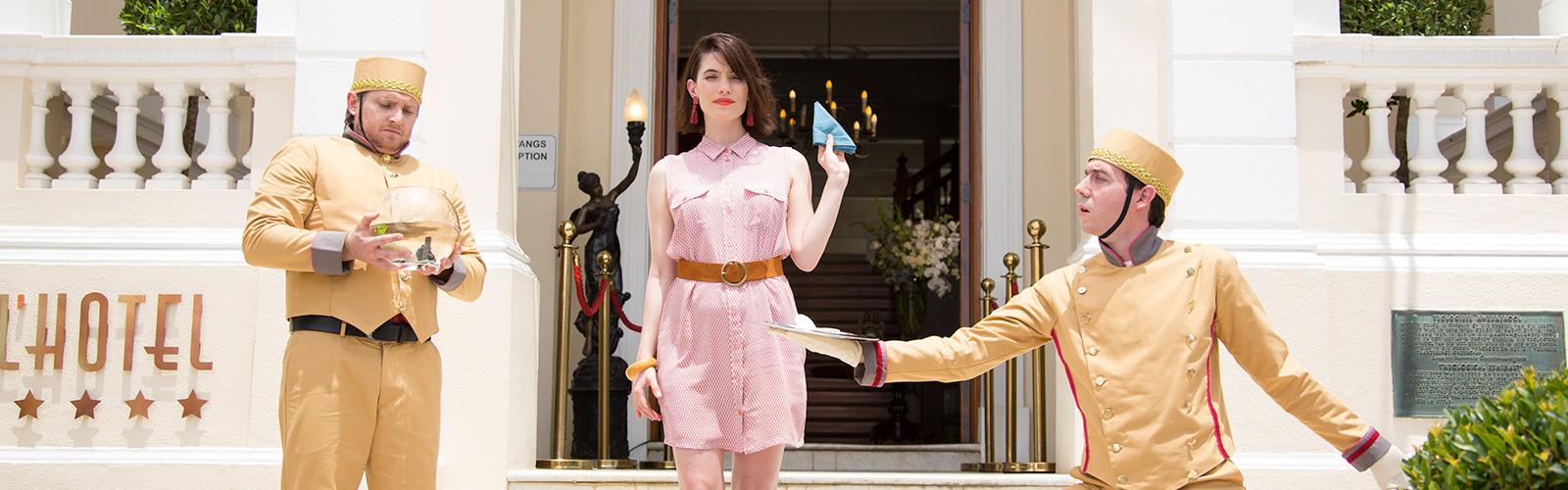 Frau zwischen zwei Hotelpagen, mit einer Serviette in der Hand.