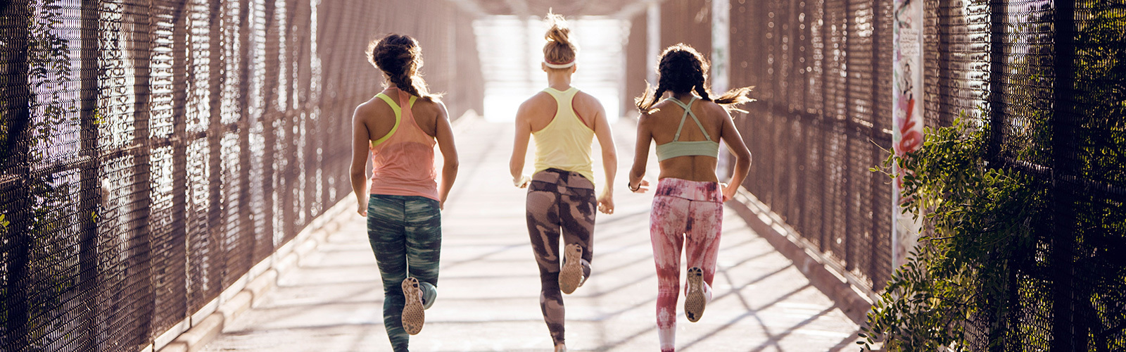 Three women running, seen from behind.
