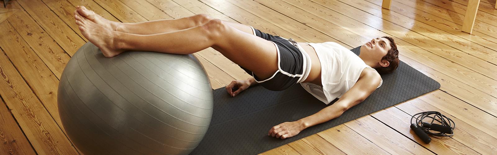 Eine Frau beim Pilates-Training mit einem Medizinball.