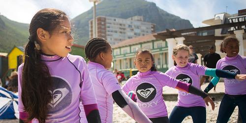 En gruppe på fem åtteårige jenter står på linje, med armene utstrakt for å holde balansen på et surfekurs for nybegynnere på stranden.