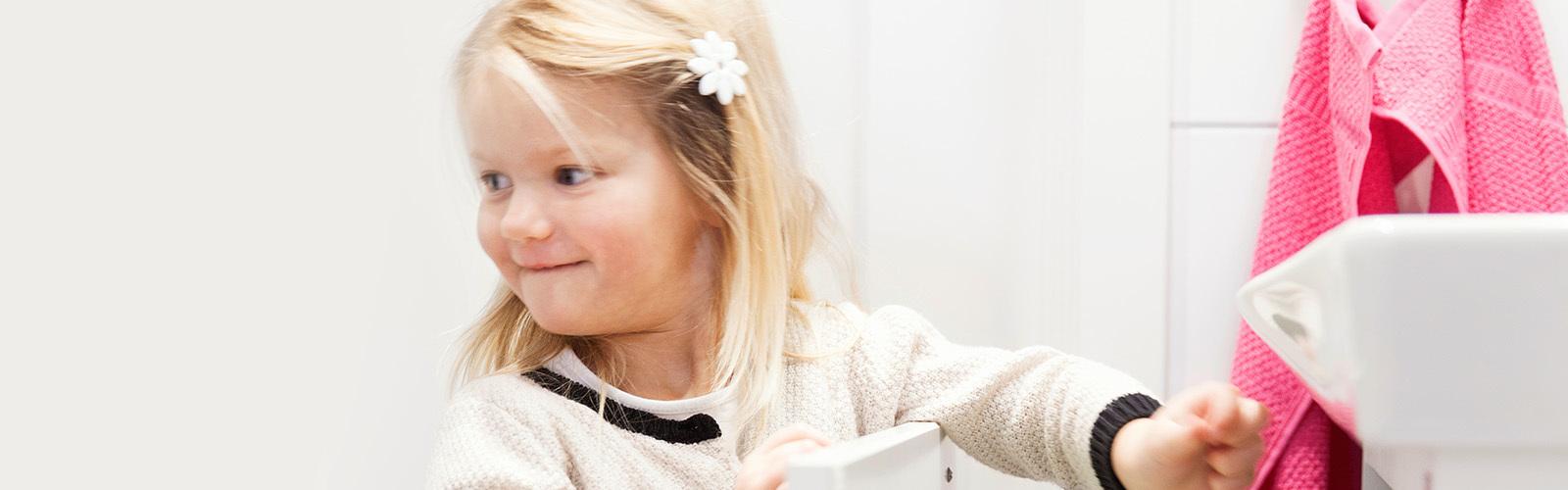 En utspekulert treåring snur seg mot noen idet hun åpner en skuff på badet, stolt over at hun klarer å gjøre det selv.