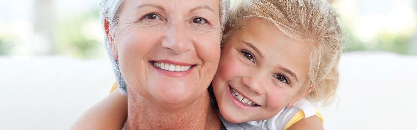 En glad, smilende mor som blir klemt bakfra av sitt glade og trygge barn.