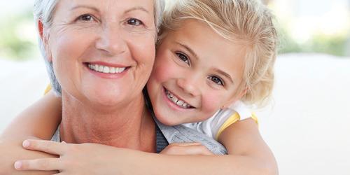 En leende mamma får en kram från sitt lyckliga och trygga barn.
