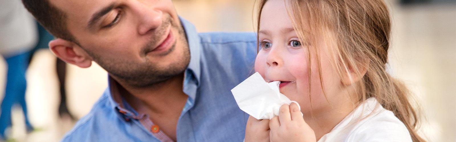 En fem år gammel jente sitter på farens fang og tørker ansiktet med en papirserviett.