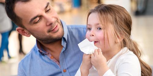En liten 5-årig flicka sitter i sin pappas knä och torkar ansiktet med en pappersnäsduk.
