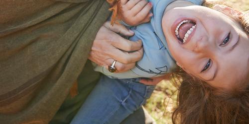 Vi ser ned på en spent fem år gammel jente som om vi var moren hennes som klemmer henne hardt mens de leker ute.