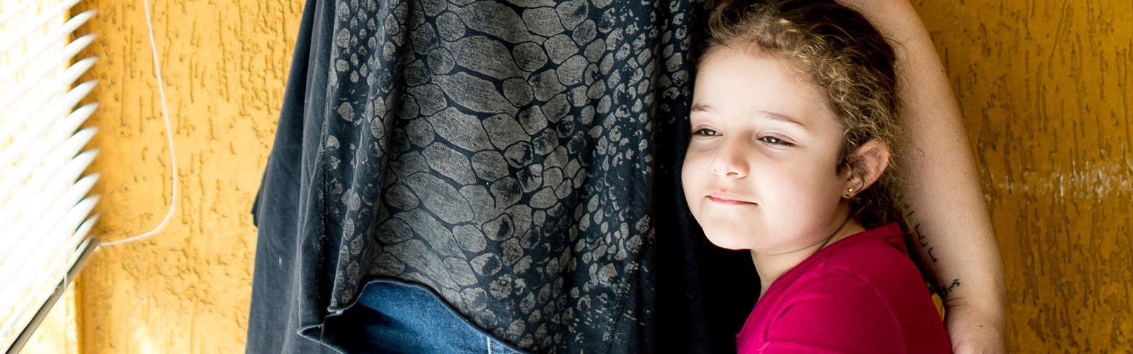 En fire år gammel jente smiler på rommet sitt, godt beskyttet av morens arm.