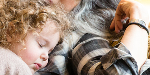 En liten 3-årig flicka med lockigt blont hår sover i knät på sin mamma