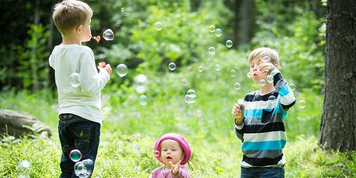 Två små bröder, 4 och 7 år, blåser såpbubblor mot varandra i en solig skogsdunge.