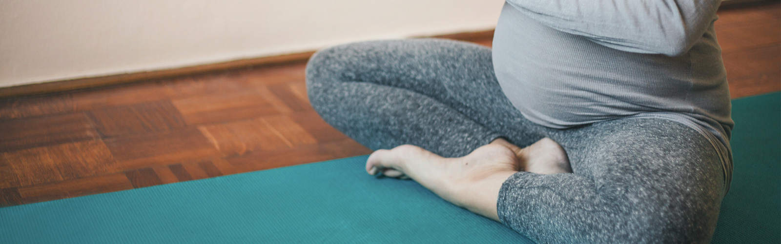 Zwangere vrouw die in een yogahouding zit