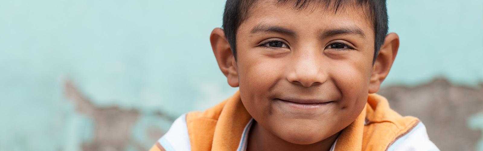 En smilende, glad, trygg og komfortabel seksårig gutt er utendørs, med en blå vegg i bakgrunnen